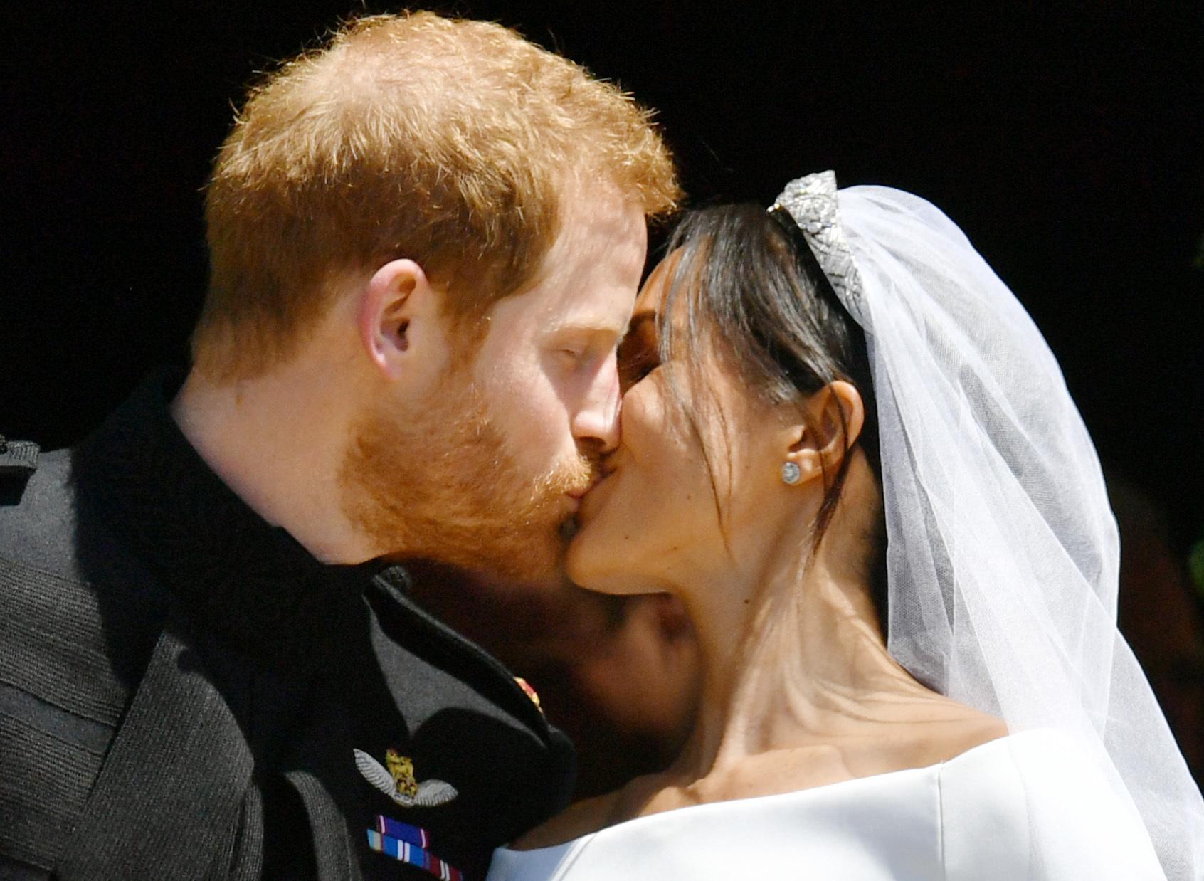 Prince Harry and Meghan Markle kiss on the steps o