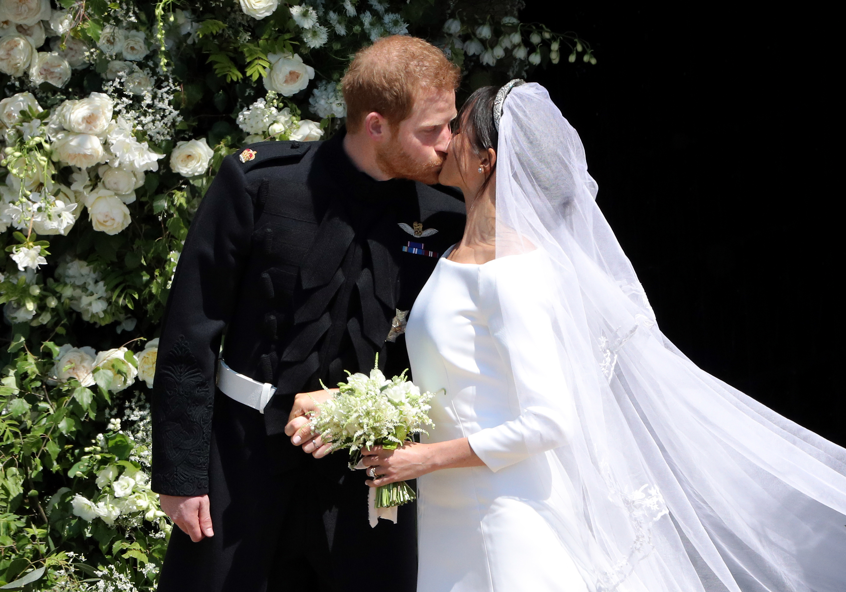 Prince Harry and Meghan Markle kiss on the steps o